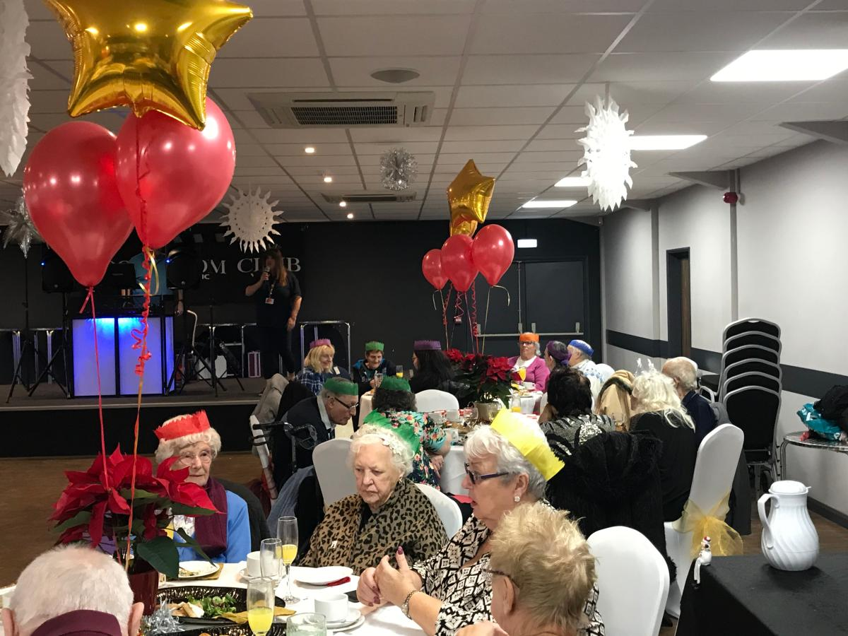 Residents chat at their tables between food and entertainment